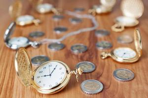 Grupo reloj de bolsillo de oro contra las monedas de euro. foto