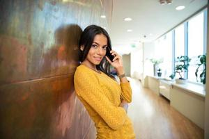 Businesswoman talking on phone in hallway