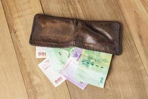 brown leather wallet with money on wood board background