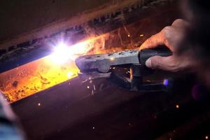 welding steel with spread spark lighting smoke photo