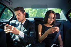Businessman and businesswoman using smartphone in car