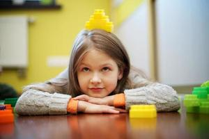 feliz hermosa niña juega con bloques foto