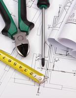 Work tools and rolls of diagrams on construction drawing