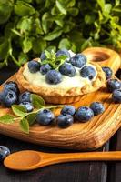 Muffin with pudding and blueberries.