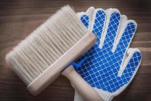 Pincel y guantes protectores sobre fondo de madera vintage co