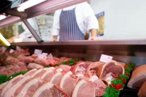 Chops in butcher's shop, butcher in background, mid section