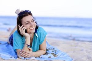 woman on the beach talking on cell photo
