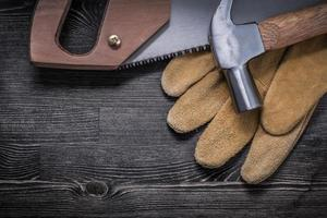 Hand saw claw hammer safety gloves on wooden board photo