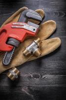 Monkey wrench pipe fittings protective gloves on wooden board photo
