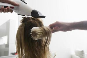 mujer secando su cabello en el salón foto