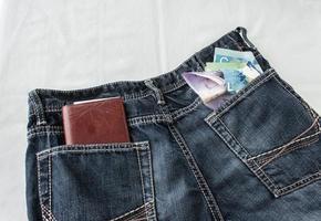 talonario de cheques y dinero en efectivo en los bolsillos de los jeans foto