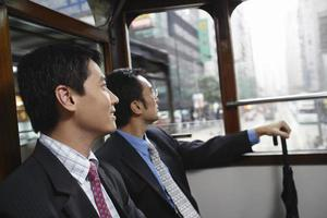 empresarios sentados en tranvía de dos pisos