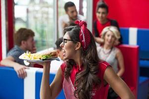 Girl with hamburger at the restaurant photo