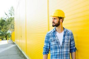 adult worker with helmet on yellow wall photo