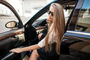 Business woman in white blouse sitting in a car
