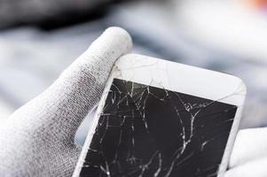 Technician holding mobile phone with broken screen