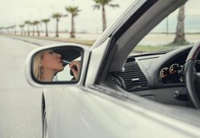 Woman apply  lipstick looking in rear view car mirror photo