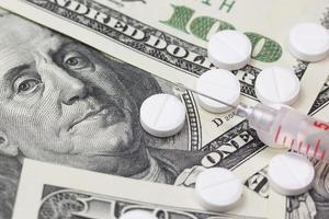Syringe and pills. US dollars in the background.