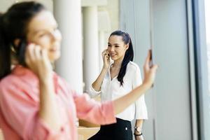 Beautiful women using phones and talkin during break photo