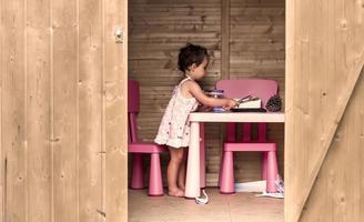 Niña pintando en una cabaña de troncos foto