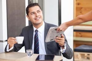 Attractive young businessman is resting in cafeteria