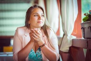 joven mujer atractiva disfrutando de una taza de café en la cafetería foto