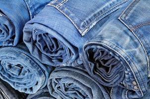 pila de jeans de colores enrollados. vista superior foto