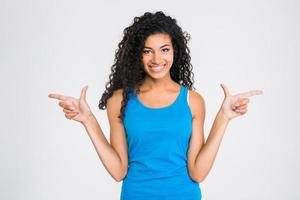 Smiling african woman pointing fingers away
