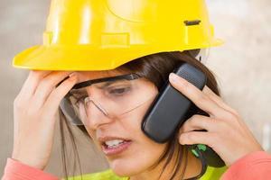Retrato de una mujer con casco de seguridad y teléfono móvil foto