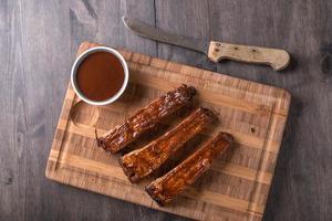 costillas en una tabla de cortar con salsa barbacoa foto