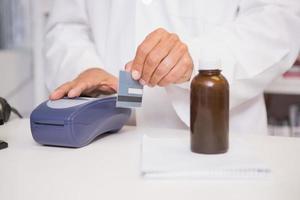 Pharmacist using keypad with credit card photo
