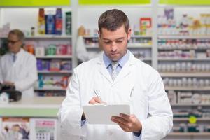 Pharmacist writing on clipboard photo