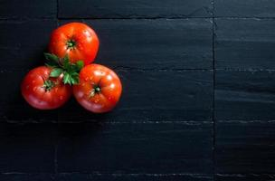tomates frescos y saludables sobre pizarra negra foto