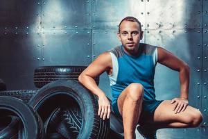 Sportsman sitting on the tire machine. Concept of gym, health