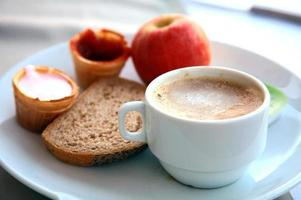 taza de capuchino con fruta, yogurt y pan