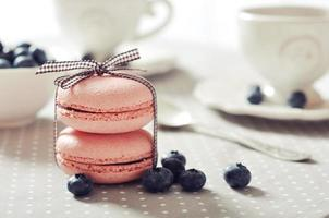 Pink macaroons tied up in ribbons with blueberries