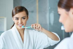 joven mujer bonita cepillarse los dientes foto