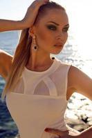 Chica con cabello rubio en elegante vestido posando en la playa