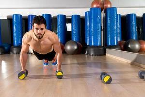 Dumbbells push-ups man at fitness gym