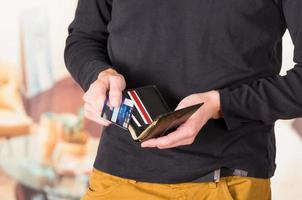 Man wearing beige jeans and dark sweater holding wallet open
