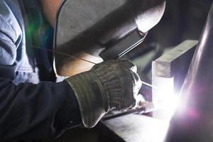 professional welder welding metal parts photo