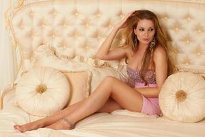 Beautiful long-haired blonde sitting on bed with pillows in dress