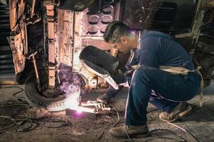 joven trabajador mecánico reparando la vieja carrocería de época foto