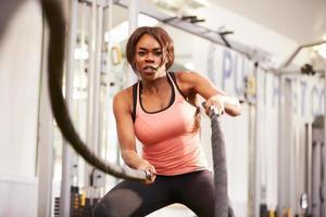 Mujer joven trabajando con cuerdas de batalla en un gimnasio foto