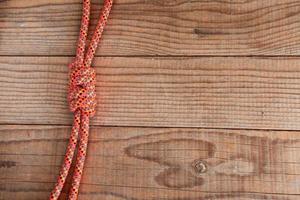 junção entre duas cordas de montanha em fundo de madeira