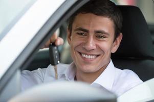 chico guapo feliz con llaves en su auto nuevo