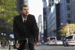 Businessman Riding Bicycle While Looking Away photo