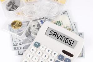 ¡monedas y monedas clasificadas con una calculadora que dice ahorros! foto