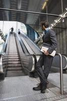 Germany, Bavaria, Munich, businessman at subway station waiting by escalator