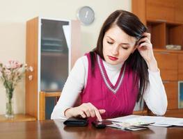 Ama de casa seria rellenando facturas de pagos de servicios públicos